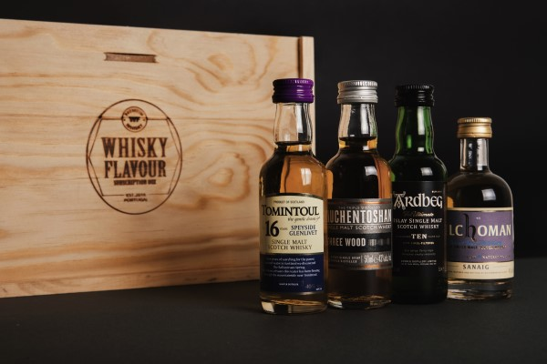 4 miniature whisky expressions near a wooden box